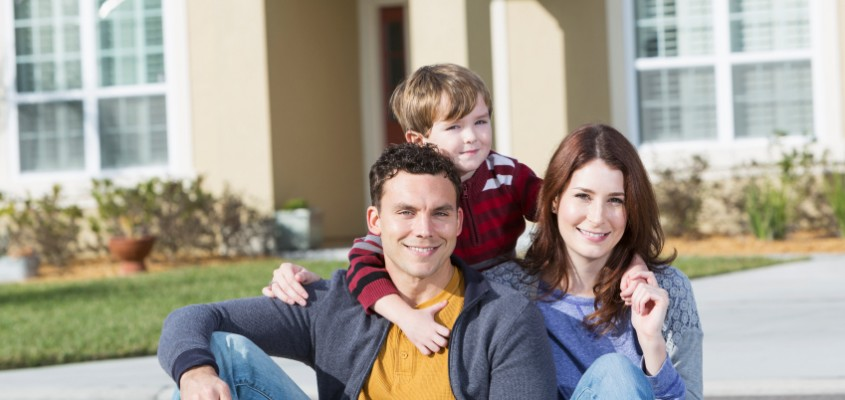 Portrait of young family sitting in front of house.