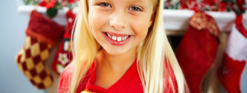 Closeup portrait of a smiling little girl holding gift with Christmas socks in the background