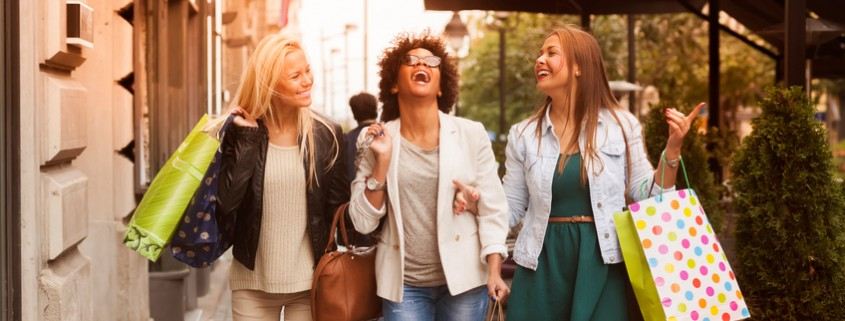 Three women holding shopping bags while walking on the street laughing and smiling