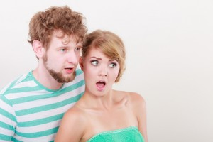 Emotional facial expression wide eyed couple, woman an man looking surprised open mouth