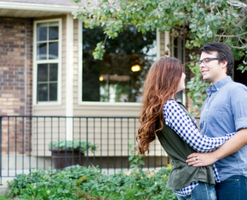 new home owners celebrate outside of their real estate purchase