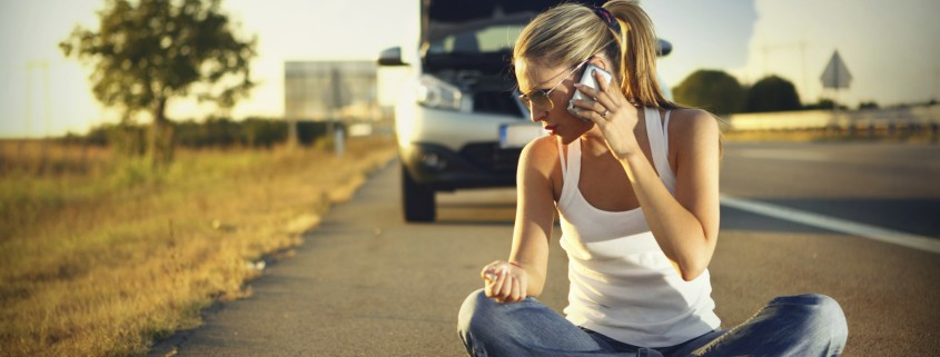woman sitting on the road and calling for help during sunset on summer day, somewhere distant and remote. Her car is in background broken.