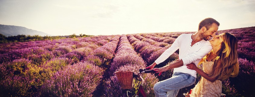 Photo of happy couple enjoying their love at the lavender field, riding a bike and kissing